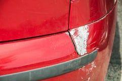 Rode gekraste auto met beschadigde verf in neerstortingsongeval of parkeerterrein en gedeukte schade van het lichaam van het bump royalty-vrije stock foto