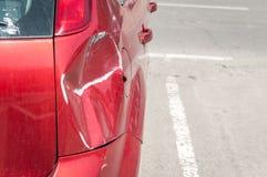 Rode gekraste auto met beschadigde verf in neerstortingsongeval of parkeerterrein en gedeukte schade van metaallichaam van botsin stock foto