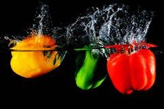 Rode gele en groene paprika'sval in water royalty-vrije stock foto's