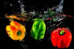 Rode gele en groene paprika'sval in water, op zwarte backgroun royalty-vrije stock foto