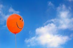 Rode gelukkige gezichtsballon met blauwe hemel athe achtergrond royalty-vrije stock fotografie