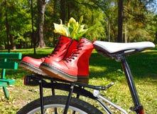 Rode geregen laarzen op fiets in park Stock Foto's