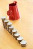 Rode gieter met muntstuk (weg in kant) Stock Foto