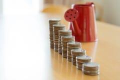 Rode gieter met muntstuk (weg in kant) Royalty-vrije Stock Foto