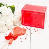 Rode giftdoos, bloemen en liefjelolly op houten backgro Stock Afbeeldingen