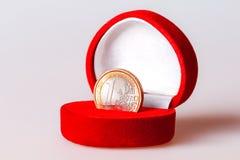 Rode giftdoos met één euro muntstuk, munt van de eurozone Stock Afbeelding