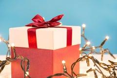 Rode giftdoos met boog en Kerstmislichten op bureau stock afbeelding