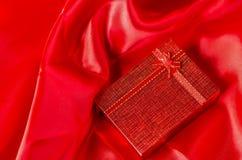 Rode giftdoos met rode lintboog op rode satijntextiel Royalty-vrije Stock Fotografie