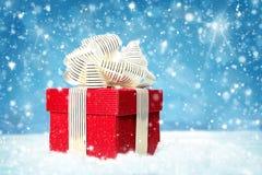 Rode giftdoos op witte sneeuw Royalty-vrije Stock Foto's