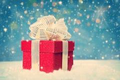 Rode giftdoos op witte sneeuw Stock Afbeelding