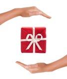 Rode Giftdoos tussen handen Royalty-vrije Stock Foto's