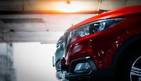 Rode glanzende die SUV-sportwagen bij winkelcomplex binnenparkeerterrein wordt geparkeerd Koplamplichten met elegant en luxeontwe stock foto's
