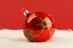 Rode glanzende Kerstmisbal met groene sterren op wit bont voor rode achtergrond Stock Foto
