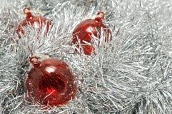 Rode glassnuisterijen op zilveren klatergoud. Stock Foto's
