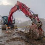 Rode graafwerktuig en barricade op een modderige die bergweg in de winter wordt bekeken stock fotografie
