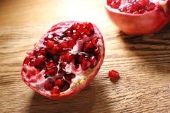 Rode granaatappel, die in twee delen, op een houten lijst wordt verdeeld hoogte in vitamine royalty-vrije stock afbeeldingen