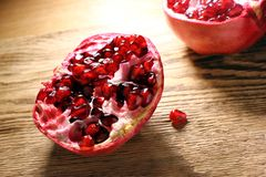 Rode granaatappel, die in twee delen, op een houten lijst wordt verdeeld hoogte in vitamine stock afbeelding