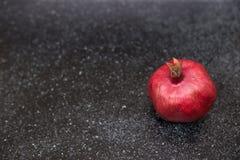 Rode granaatappel op zwarte achtergrond Stock Foto