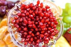 Rode granaatappelzaden in een kom met verse vruchten stock afbeeldingen