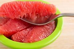 Rode grapefruitplakken in een groene kom met lepel Stock Foto