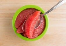 Rode grapefruitsecties in een groene kom met lepel Stock Fotografie