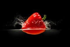 Rode groene paprika die in water op zwarte vallen Stock Foto's