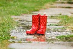 Rode gumboots in regen Stock Foto's