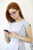 Rode haarvrouw met cellphone stock afbeeldingen
