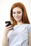 Rode haarvrouw met cellphone Royalty-vrije Stock Foto's