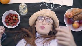 Rode haired jonge vrouw die grappige gezichten maken en selfies in park liggen stock footage