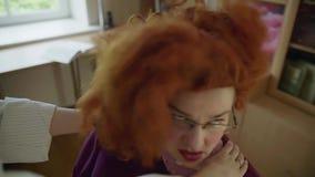 Rode haired vrouw die door vrouwelijke handen worden versperd stock videobeelden