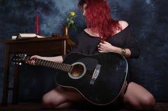 Rode haired vrouw en de zwarte akoestische gitaar Royalty-vrije Stock Foto