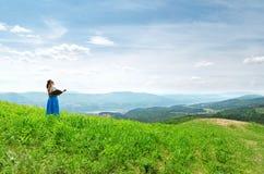Rode haired vrouw met boek op de heuveltop stock fotografie