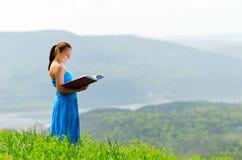 Rode haired vrouw met boek op de heuveltop stock afbeeldingen