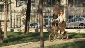Rode haired vrouwen berijdende fiets in stadspark op zonnige dag royalty-vrije stock foto