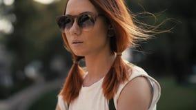 Rode haired vrouwen berijdende fiets in stadspark op zonnige dag stock afbeeldingen