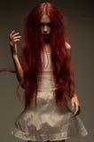 Rode haired zombievrouw in witte katoenen kleding royalty-vrije stock foto