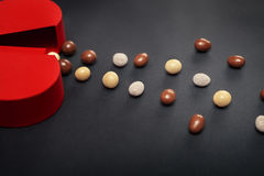 Rode hart gevormde doos met chocoladedragees op donkere achtergrond Stock Fotografie