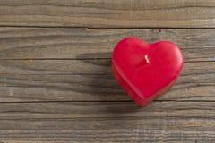 Rode hart gevormde kaars op een houten oppervlakte royalty-vrije stock foto