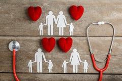 Rode hart, stethoscoop en document kettingsfamilie op houten lijst Royalty-vrije Stock Foto's