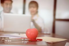 Rode hart & stethoscoop op bureau met arts die geduldig t bespreken Stock Foto