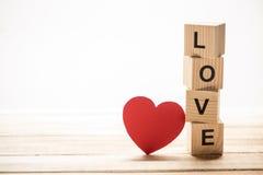 Rode hartdocument besnoeiing en houten kubussen Stock Fotografie