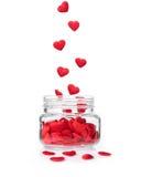 Rode harten die in glaskruik vallen, valentijnskaartconcept Stock Afbeelding