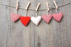 Rode harten die over houten achtergrond hangen Royalty-vrije Stock Afbeeldingen