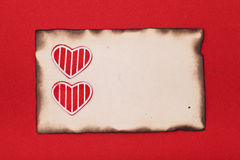 Rode harten en gebrand document Stock Foto's