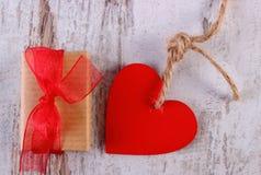 Rode harten met verpakte gift voor Valentijnskaartendag op oude houten oppervlakte Royalty-vrije Stock Foto