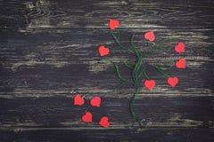 Rode harten op een boom van draad Beeld van een boom met rode harten op een zwarte houten achtergrond Stock Foto
