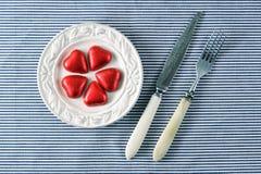 Rode harten op een plaat en een mes met een vork Royalty-vrije Stock Fotografie