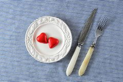 Rode harten op een plaat en een mes met een vork Royalty-vrije Stock Afbeelding