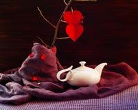 Rode harten op een tak en een witte ketel op een purpere achtergrond, het concept de Dag van Valentine ` s, zijaanzicht Royalty-vrije Stock Foto